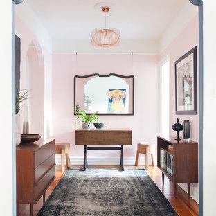 Неиссякаемый источник вдохновения для домашнего уюта: фойе в стиле фьюжн с розовыми стенами, паркетным полом среднего тона и коричневым полом