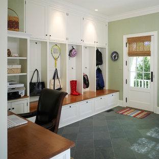 Inredning av ett klassiskt mellanstort kapprum, med gröna väggar, skiffergolv, en enkeldörr, en vit dörr och svart golv