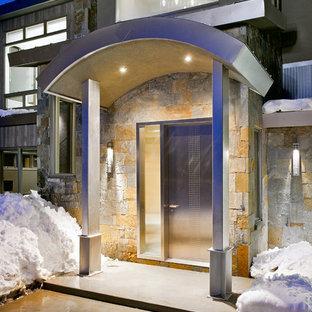 Modelo de puerta principal contemporánea, de tamaño medio, con puerta simple, puerta metalizada, paredes multicolor, suelo de cemento y suelo gris