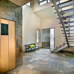 Réalisation d'un grand hall d'entrée design avec une porte simple, une porte métallisée, un mur gris, un sol gris et un sol en ardoise.