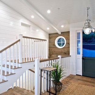 Modelo de distribuidor costero, de tamaño medio, con paredes blancas, suelo de madera clara, puerta doble y puerta verde