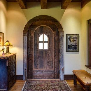 Exemple d'un hall d'entrée craftsman de taille moyenne avec un sol en bois brun, une porte pivot et une porte en bois foncé.
