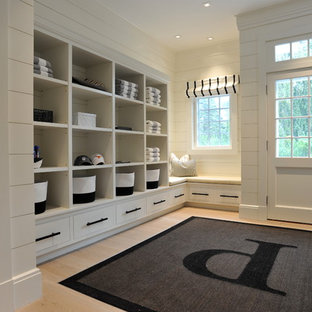 Design ideas for a beach style mudroom in New York with white walls, light hardwood floors, a single front door and a white front door.