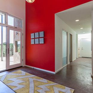 アルバカーキの中サイズの両開きドアコンテンポラリースタイルのおしゃれな玄関ロビー (赤い壁、コンクリートの床) の写真