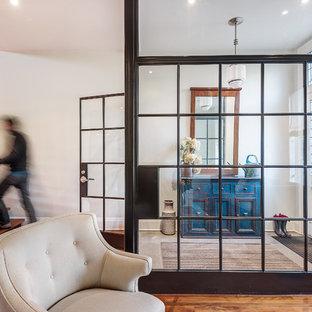 Industriell inredning av en mellanstor foajé, med vita väggar, ljust trägolv, en enkeldörr och en vit dörr
