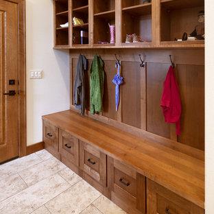 Klassisk inredning av ett mellanstort kapprum, med vita väggar, klinkergolv i porslin, en enkeldörr, mellanmörk trädörr och beiget golv