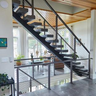 Immagine di un ingresso moderno di medie dimensioni con pareti bianche, pavimento con piastrelle in ceramica, una porta a due ante, una porta in vetro, pavimento grigio e soffitto in legno
