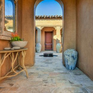 ロサンゼルスの中くらいの片開きドア地中海スタイルのおしゃれな玄関ドア (マルチカラーの壁、トラバーチンの床、濃色木目調のドア) の写真