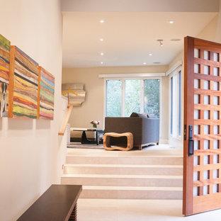 Foto på en stor funkis ingång och ytterdörr, med beige väggar, en enkeldörr, klinkergolv i porslin, mellanmörk trädörr och beiget golv