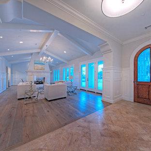 На фото: большое фойе в средиземноморском стиле с белыми стенами, полом из травертина, одностворчатой входной дверью и входной дверью из дерева среднего тона с
