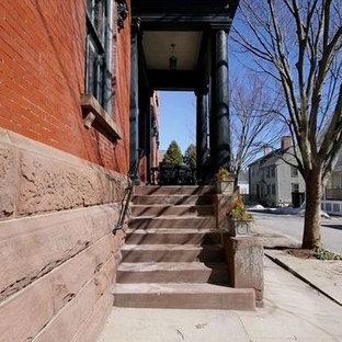 ニューヨークの大きい両開きドアインダストリアルスタイルのおしゃれな玄関ドア (トラバーチンの床、濃色木目調のドア、赤い壁) の写真