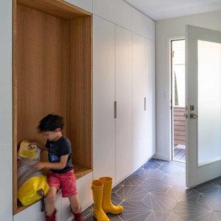 ニューヨークの片開きドアミッドセンチュリースタイルのおしゃれなマッドルーム (白い壁、磁器タイルの床、ガラスドア、グレーの床) の写真