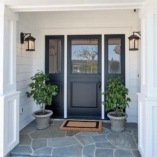 Ejemplo de puerta principal marinera, grande, con paredes blancas, puerta tipo holandesa y puerta negra