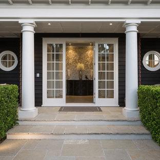 Свежая идея для дизайна: большая входная дверь в морском стиле с черными стенами, одностворчатой входной дверью, паркетным полом среднего тона, стеклянной входной дверью и коричневым полом - отличное фото интерьера