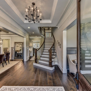 Example of a large transitional dark wood floor, tray ceiling and wainscoting entryway design in Charlotte with a dark wood front door