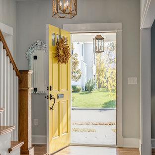 Immagine di un ingresso american style di medie dimensioni con pareti grigie, una porta singola, una porta gialla e pavimento in legno massello medio