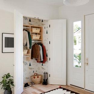 Eklektisk inredning av en foajé, med vita väggar, ljust trägolv, en enkeldörr, en vit dörr och beiget golv