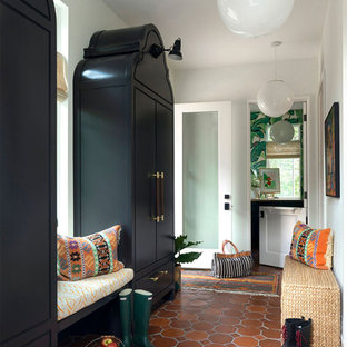 Eclectic terra-cotta tile and orange floor mudroom photo in Minneapolis with white walls and a glass front door