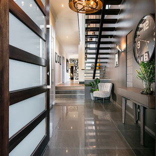 パースの片開きドアコンテンポラリースタイルのおしゃれな玄関ロビー (黒い壁、濃色木目調のドア、グレーの床) の写真