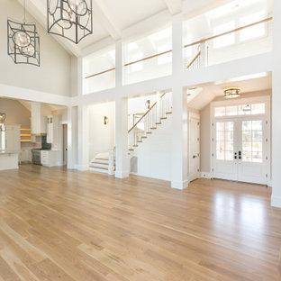 Aménagement d'un hall d'entrée bord de mer avec un mur beige, un sol en bois brun, une porte double, une porte bleue, un sol marron, un plafond voûté et du lambris de bois.