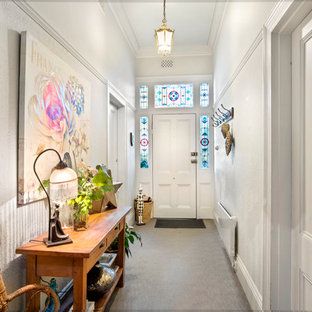 Design ideas for an eclectic entry hall in Melbourne with white walls, a single front door, a white front door and grey floor.