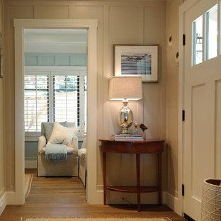 Ejemplo de entrada costera con paredes beige, puerta simple, puerta blanca y suelo de madera en tonos medios