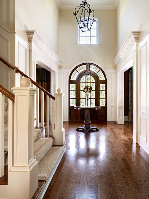 Example Of A Classic Dark Wood Floor Entryway Design In Charlotte With  Beige Walls And A