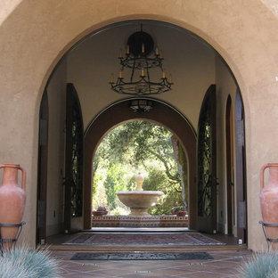 Aménagement d'une grand porte d'entrée méditerranéenne avec un mur beige, un sol en carreau de terre cuite, une porte double et une porte en verre.