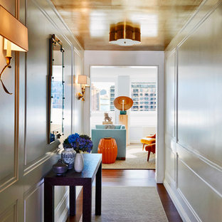 Example of a mid-sized transitional brown floor and dark wood floor entryway design in New York with white walls