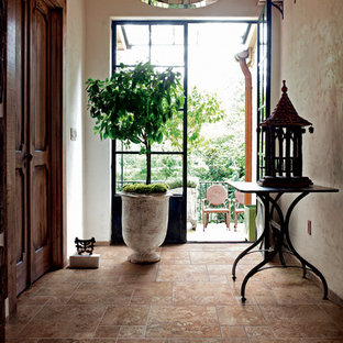 Example of a large tuscan porcelain tile and brown floor entryway design in Other with beige walls and a dark wood front door