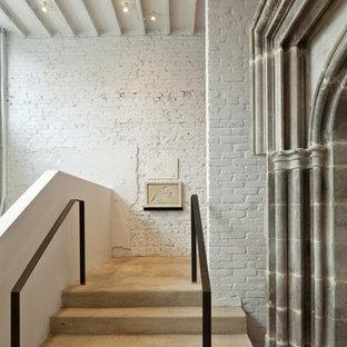 Ejemplo de distribuidor urbano, extra grande, con paredes blancas, suelo de cemento, puerta simple y puerta negra