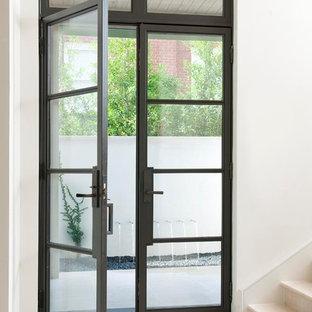 Immagine di un ingresso o corridoio minimal con una porta a due ante, una porta in vetro e pavimento bianco
