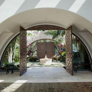 Imagen de puerta principal mediterránea, extra grande, con paredes blancas, suelo de piedra caliza, puerta doble y puerta de madera en tonos medios