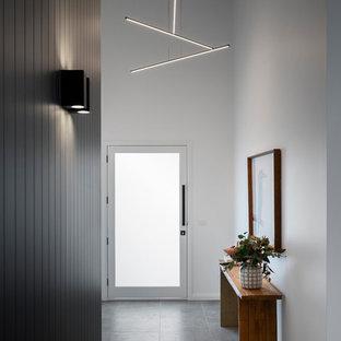 Свежая идея для дизайна: входная дверь среднего размера в стиле модернизм с желтыми стенами, полом из керамогранита, одностворчатой входной дверью, стеклянной входной дверью и серым полом - отличное фото интерьера