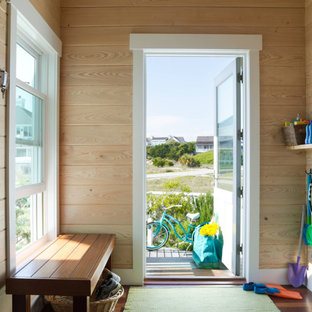 Inspiration for a beach style medium tone wood floor single front door remodel in Miami with a glass front door
