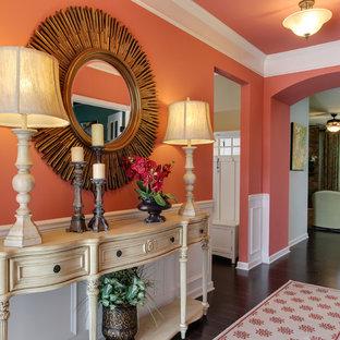 На фото: узкая прихожая среднего размера в стиле фьюжн с оранжевыми стенами, темным паркетным полом и коричневым полом