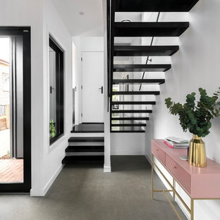 Trendy concrete floor and gray floor entryway photo in Brisbane with white walls and a white front door