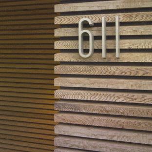 Exemple d'une petit porte d'entrée moderne avec un mur marron, une porte en bois foncé, un sol en bois foncé et une porte simple.