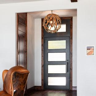 Mittelgroßer Rustikaler Eingang mit Foyer, beiger Wandfarbe, dunklem Holzboden, Einzeltür, schwarzer Tür, braunem Boden und freigelegten Dachbalken in Dallas