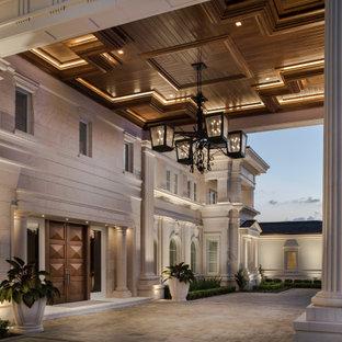 オーランドの巨大な両開きドアトランジショナルスタイルのおしゃれな玄関 (大理石の床、濃色木目調のドア、ベージュの床、格子天井) の写真