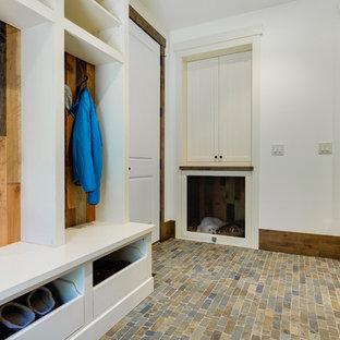 На фото: маленький тамбур в стиле рустика с белыми стенами и полом из сланца с