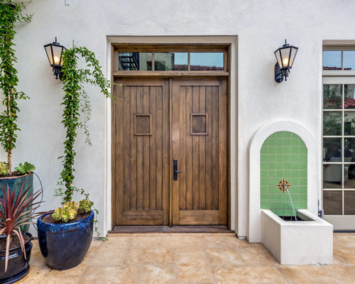 example of a tuscan entryway design in los angeles with white walls and a dark wood - Front Door Design Ideas