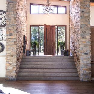 Modelo de puerta principal actual, extra grande, con paredes beige, suelo de madera oscura, puerta pivotante, puerta de madera en tonos medios y suelo marrón