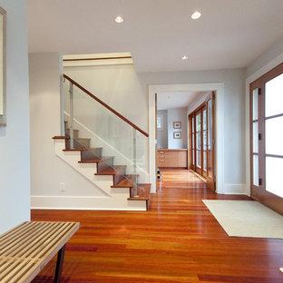 Idée de décoration pour un hall d'entrée design avec un sol en bois brun, une porte simple, une porte en verre et un sol orange.