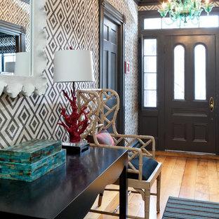 Immagine di un ingresso o corridoio boho chic con pavimento in legno massello medio, una porta singola, una porta nera e pareti multicolore
