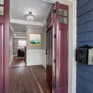 Foto di un corridoio chic con pareti blu, pavimento in legno massello medio, una porta singola e una porta rossa