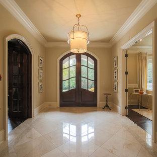 Geräumiger Klassischer Eingang mit Foyer, beiger Wandfarbe, Marmorboden, Doppeltür, dunkler Holztür und beigem Boden in Charlotte