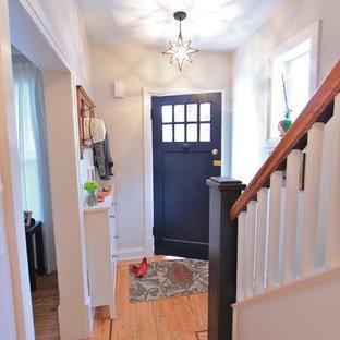 Bild på en liten eklektisk ingång och ytterdörr, med en blå dörr, grå väggar, ljust trägolv och en enkeldörr