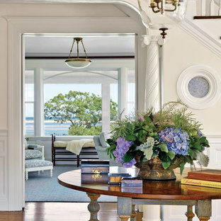 Example of a large beach style medium tone wood floor entry hall design in Boston with white walls