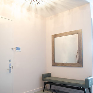 Entryway - mid-sized contemporary granite floor entryway idea in New York with white walls and a white front door